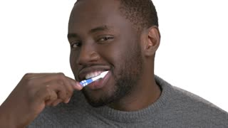 Black man brushing teeth. Process of cleaning teeth by dark skinned man on white background. Concept of oral hygiene and dental care.