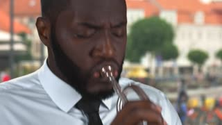 Black man playing trumpet. Musician on street background.