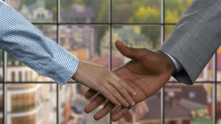 Black man shaking businesswoman's hand. Business handshake on urban background. Starting career in big company. New employees have good perspectives.
