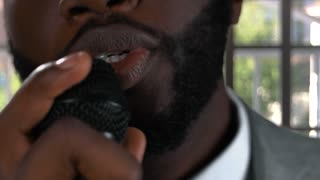 Black man singing. Guy with microphone closeup. Singer in the studio.