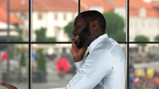 Black man talking on phone. Businessman on urban background. Leading the discussion.