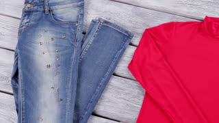 Blue jeans and red top. Colorful top with long sleeves. Clothes bought at brand store. Gray wooden table with clothing.