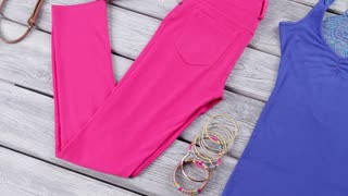 Blue top and pink pants. Bracelets and wedge sandals. Girl's trendy summer apparel. Bijouterie and clothing on shelf.