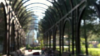 Blurred arches and trees. Blurry people on park benches.