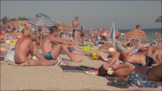 Blurry summer beach, daytime. People sitting near the sea.