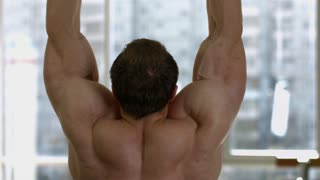 Bodybuilder in gym. Man doing pull-ups. Bodybuilder stands by for competition. A sight from the window on the background.
