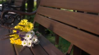Bouquet on brown bench. White and yellow flowers. Lilac and camomiles. Summer has come.