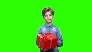 Boy in denim jacket with red gift box. Green hromakey background for keying.