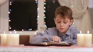 Boy praying at the table. Kid prays at nighttime. Christmas prayer at city church. Youthful parishioner on Christmas.