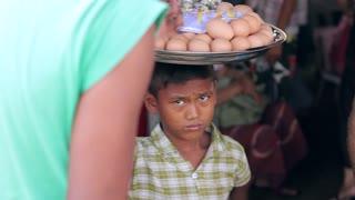 Boy sells eggs on market.