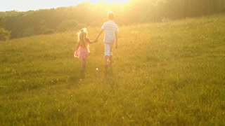 Boy with girl walk on evening meadow. Golden sunset.