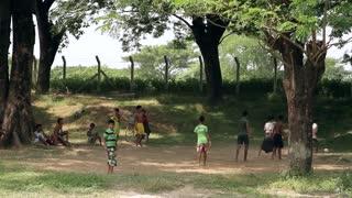 Boys barefoot on sand playing football.