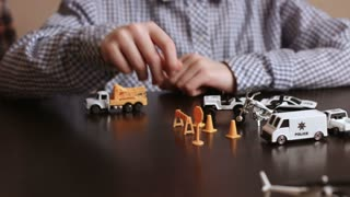 Boy's hand moves toy vehicle. Kid playing with toy cars. Re-creating work of police. Law enforcement in miniature.