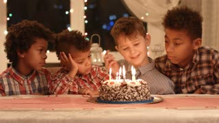 Boys near cake with candles. Kids sitting at the table. Company of friends celebrates birthday. Wish you all the good.
