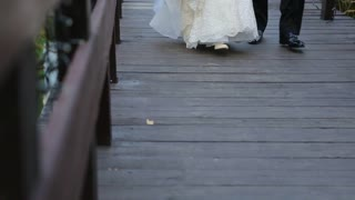 Bride and groom are on the a wooden bridge.