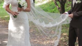 Bride and groom on their wedding. Groom holding bride's wedding veil. Wedding ceremony.