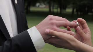 Bride putting wedding ring on grooms finger Young couple at