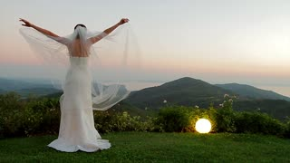 Bride standing on background of beautiful landscape. Bride enjoying the sunset.
