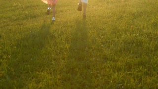 Brother and sister playing in the meadow. Boy and girl holding hands.