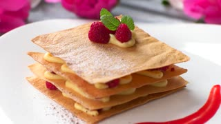 Brown powder falls on cake. Dessert with mint and berries. Raspberry millefeuille with cinnamon. Baked food in french cafe.