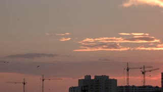 Buildings and cranes, sunset background. Rooftop of apartment block. Top building companies.