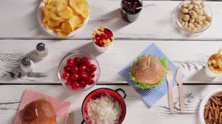 Burger and bowl of pickles. Fast food with fresh vegetables. Different products and refreshing beverage. White table filled with food.