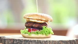 Burger on wooden board. Delicious beef burger with egg.