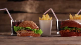 Burgers with beverages and fries. Tasty junk food on table. Bright colors of satiety. Just have a bite.
