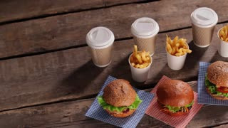Burgers with fries and drinks. Top view of bistro table. Fast food restaurant's morning menu. Fresh food and hot drinks.