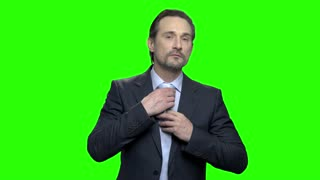 Business man adjusting his tie. Handsome middle aged mature man in suit. Green hromakey background for keying.