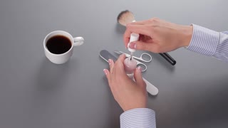 Business woman covers nail of polish. Clerk makes a manicure on the workplace. French manicure in the office.