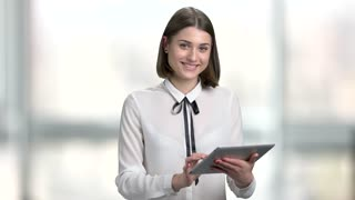 Business woman with tablet on blurred background. Young pretty girl wearing white blouse searching an information in internet via digital tablet and smiling. People, technology, business.