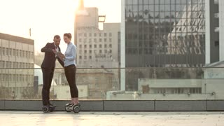 Businessman and woman, city background. People on hoverboards with tablet. Shape the future of business.