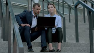 Businessman and woman with laptop. People sitting on stairs. Possibilities around us.