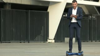 Businessman on gyroboard. Man holding tablet outdoor. Motion is success.