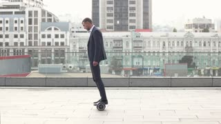 Businessman on hoverboard, slow motion. Man in a suit outdoors. The modern life.