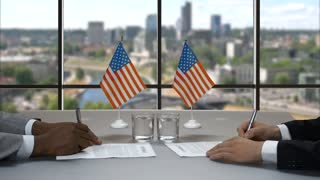 Businessmen signing papers at table. Men shake hands near flags. Common goals in politics. Work of US government.