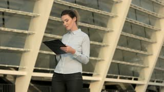 Businesswoman holding a clipboard. Young female writing. How to write a cv.