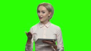 Businesswoman using electronic tablet and talking. Green screen hromakey background for keying.