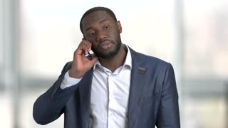 Busy black businessman appointing a meeting by phone. Afro american middle aged man in suit having business conversation. Bright blurred windows background.