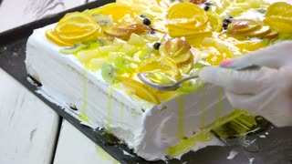 Cake decoration at restaurant cuisine. Slow motion confectioner woman is preparing delicious cake. Festive cake with variety of fruits.