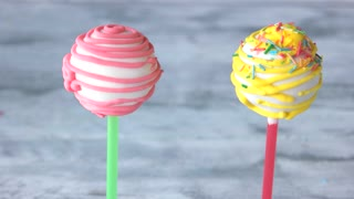 Cake pops with filling on grey background. Multicolored sweets on sticks. Delicious treats for kids.