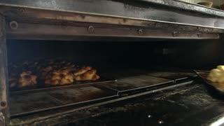 Cakes are baking in oven at bakery. Chef taking out baked pastry from oven. Baked goods manufacturing.