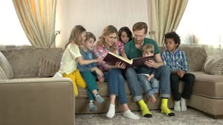 Caucasian family reading a book. Adults and children, room.