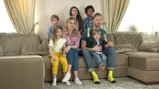 Caucasian family watching tv. People sitting in the room. Most interesting movies.