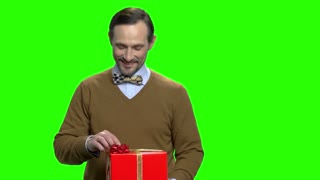Caucasian man showing gift box. Portrait of handsome middle aged man with present. Green screen hromakey background for keying.