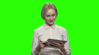 Caucasian mature businesswoman with tablet and pen. Green screen hromakey background for keying.