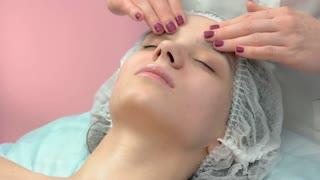 Caucasian woman, facial massage. Work of masseuse close up.