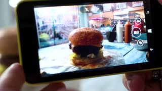 Cell phone photographing a burger. Hamburger on cafe table. The highest resolution.