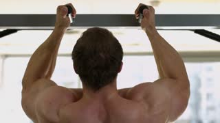 Champion doing pull-ups. Strong man doing pull-ups. Muscular back of bodybuilder training.